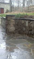 Irregular Stone patio with a retaining wall and a seat wall