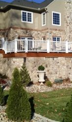 Entire house with stone, patio,fire place, boarder wall under the deck with columns